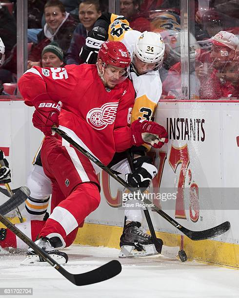 Danny DeKeyser of the Detroit Red Wings battles along the boards for the puck with Tom Kuhnhackl of the Pittsburgh Penguins during an NHL game at Joe...