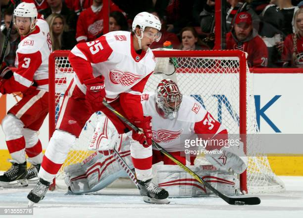 Danny DeKeyser of the Detroit Red Wings collects a puck ahead of Petr Mrazek during an NHL game against the Carolina Hurricanes on February 2 2018 at...