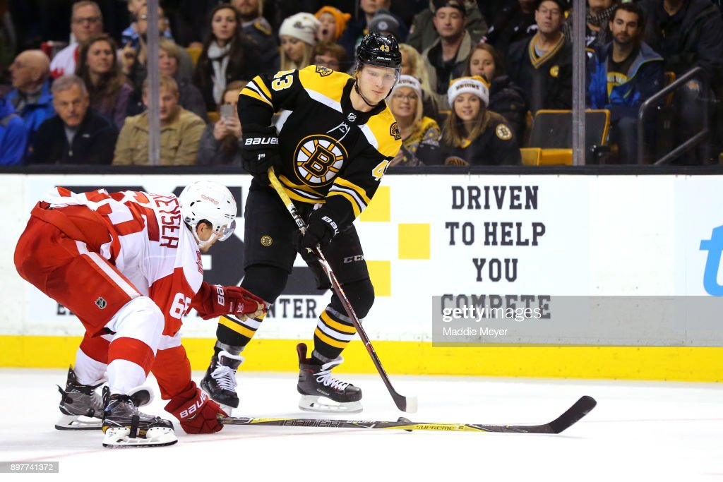 Danny DeKeyser #65 of the Detroit Red Wings defends Danton Heinen #43 of the Boston Bruins during the third period at TD Garden on December 23, 2017 in Boston, Massachusetts. The Bruins defeat the Red Wings 3-1.