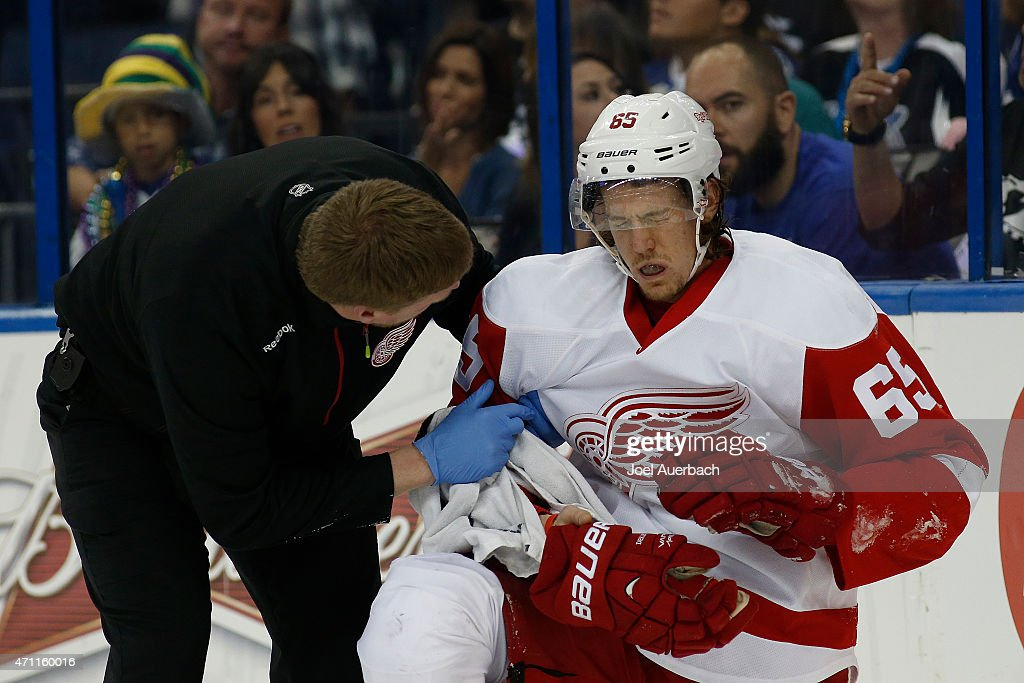 Danny DeKeyser #65 of the Detroit Red Wings is checked by a trainer after being injured by a high stick by the Tampa Bay Lightning during the second period in Game Five of the Eastern Conference Quarterfinals during the 2015 NHL Stanley Cup Playoffs at the Amalie Arena on April 25, 2015 in Tampa, Florida.
