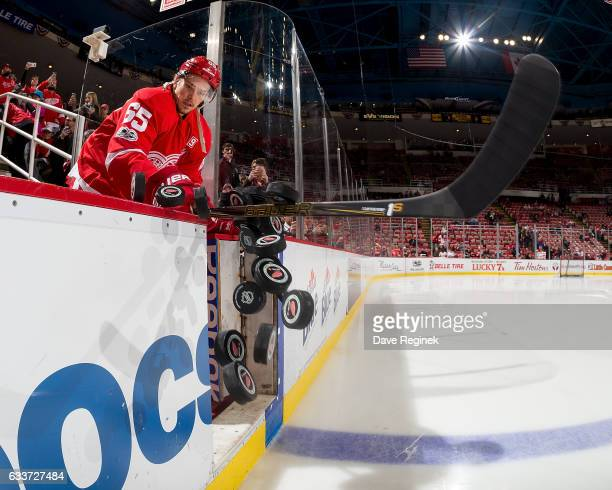 Danny DeKeyser of the Detroit Red Wings knocks the pucks onto the ice at the start of warmups prior to an NHL game against the New York Islanders at...