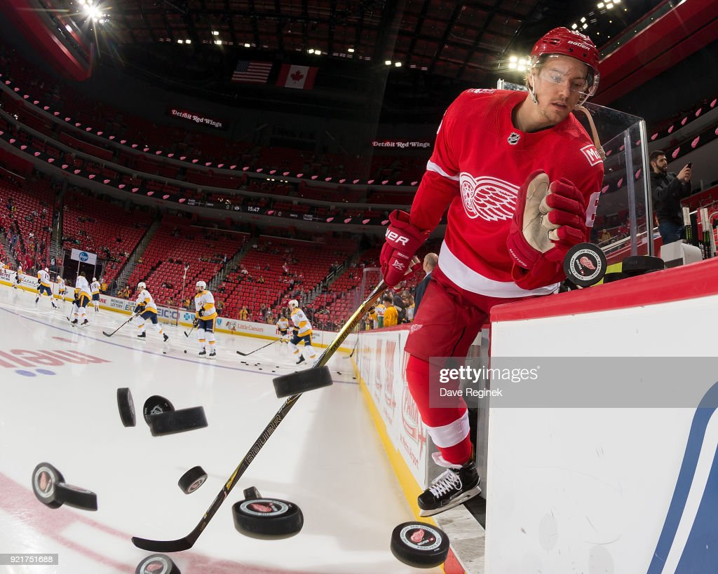Danny DeKeyser #65 of the Detroit Red Wings pushes the pucks onto the ice during warm-ups prior to an NHL game against the Nashville Predators at Little Caesars Arena on February 20, 2018 in Detroit, Michigan.