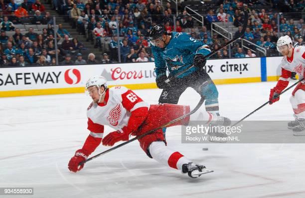 Danny DeKeyser of the Detroit Red Wings skates after the puck against Evander Kane of the San Jose Sharks at SAP Center on March 12 2018 in San Jose...