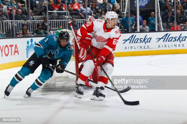 Danny DeKeyser of the Detroit Red Wings skates with the puck against Evander Kane of the San Jose Sharks at SAP Center on March 12 2018 in San Jose...