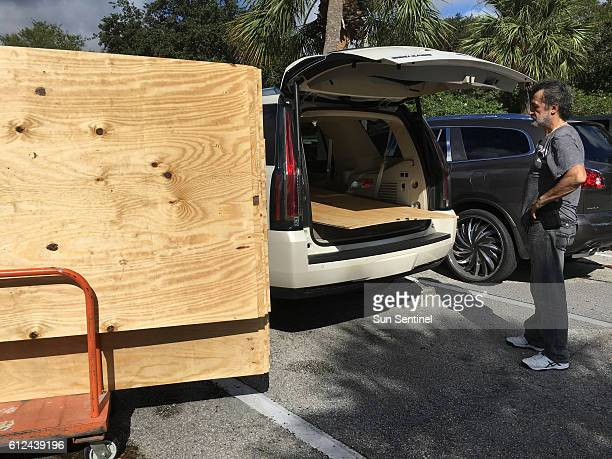 Danny Delarocca of Boca Raton Fla loads plywood onto his brother's car at the Home Depot in Deerfield Beach on Tuesday Oct 4 2016 As Hurricane...