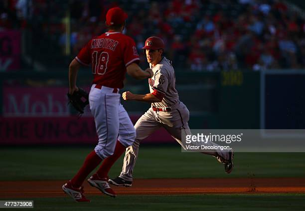 Danny Dorn of the Arizona Diamondbacks runs by Kyle Kubitza of the Los Angeles Angels of Anaheim to third from second on a single by David Peralta of...