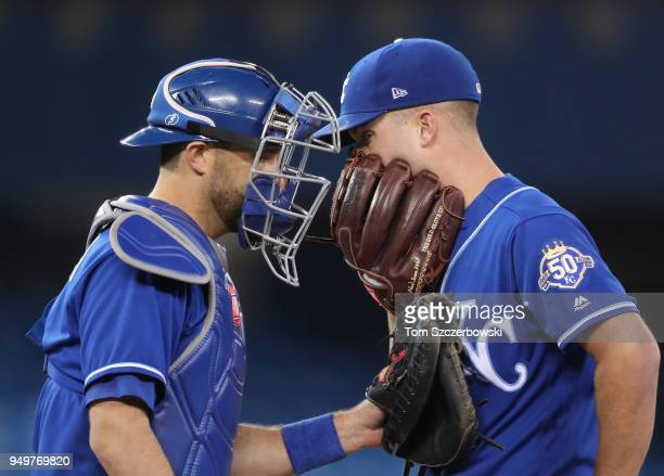 Danny Duffy of the Kansas City Royals meets on the mound with Drew Butera in the third inning during MLB game action against the Toronto Blue Jays at...