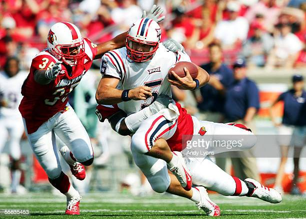 Danny Embick of Florida Atlantic Owls is sacked by Zach Anderson and Brandon Sharp of the Louisville Cardinals during the game at Papa John's Stadium...