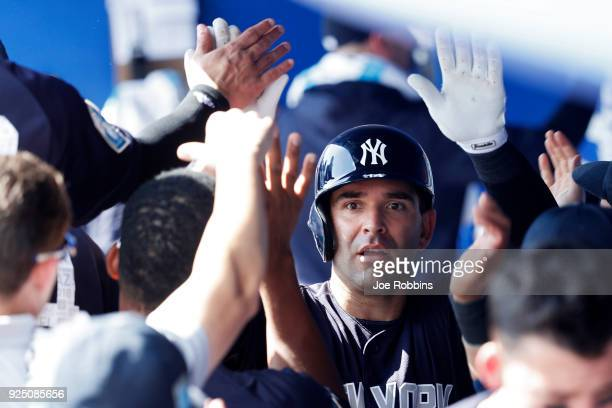 Danny Espinosa of the New York Yankees celebrates with teammates in the dugout after hitting a solo home run in the fourth inning of a Grapefruit...