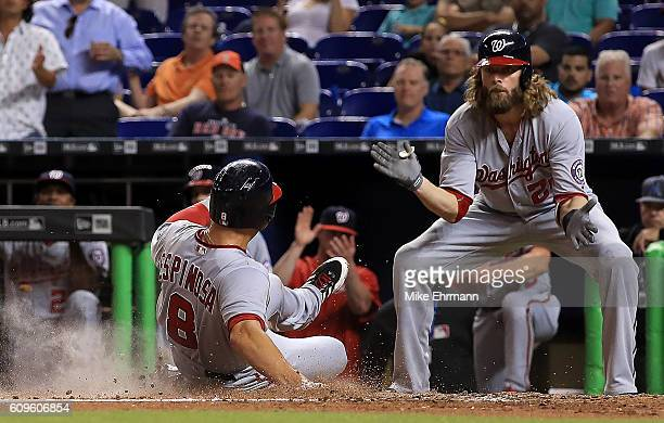 Danny Espinosa of the Washington Nationals is greeted at the plate by Jayson Werth after scoring on an error during a game against the Miami Marlins...