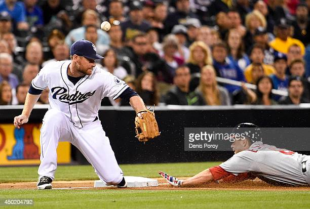 Danny Espinosa of the Washington Nationals slides into third base with a triple as Chase Headley of the San Diego Padres loses the ball during the...