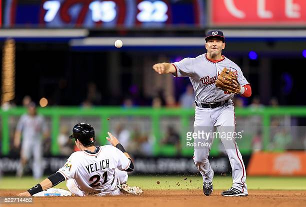 Danny Espinosa of the Washington Nationals turns a double play over Christian Yelich of the Miami Marlins during the fourth inning of the game at...