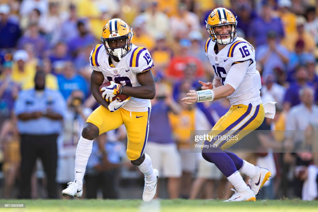Danny Etling #16 hands off the ball to Derrick Dillon #19 of the LSU Tigers during a game against the Auburn Tigers at Tiger Stadium on October 14, 2017 in Baton Rouge, Louisiana. The LSU defeated the Auburn 27-23.
