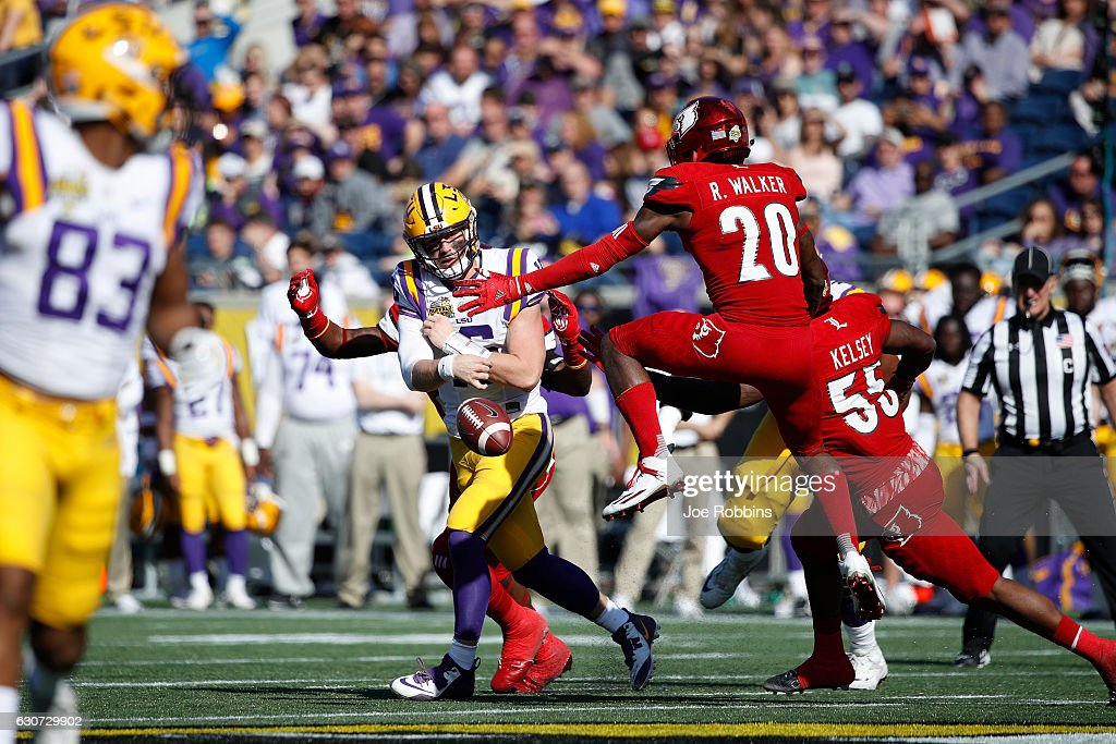 Danny Etling #16 of the LSU Tigers throws the ball away while under pressure from Ronald Walker #20 of the Louisville Cardinals in the fourth quarter of the Buffalo Wild Wings Citrus Bowl at Camping World Stadium on December 31, 2016 in Orlando, Florida. LSU defeated Louisville 29-9.