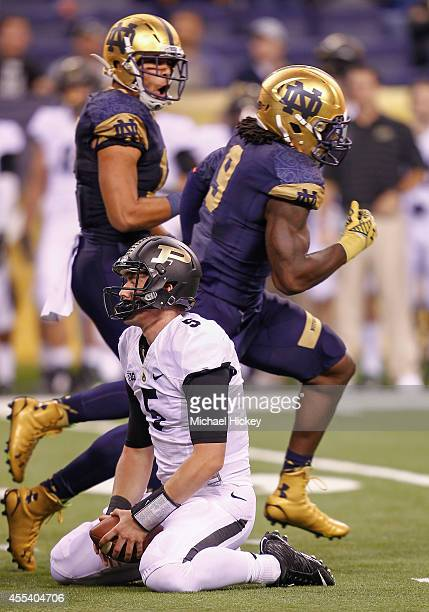 Danny Etling of the Purdue Boilermakers sits on the ground after a sack as James Onwualu and Jaylon Smith of the Notre Dame Fighting Irish celebrate...