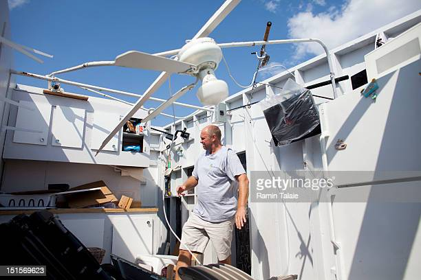 Danny Fallon of Brooklyn, New York inspects the damage in his rental cabana where a tornado touched down on September 8, 2012 in the Breezy Point...