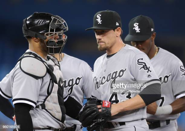 Danny Farquhar of the Chicago White Sox waits on the mound to be relieved by manager Rick Renteria as Welington Castillo looks on in the seventh...