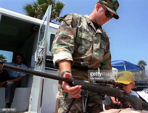 Danny Fisher of Port Hueneme takes a look thru scope attached to a Remington 700 police sniper rifle as Scott Hebert of the Ventura County Swat Team...