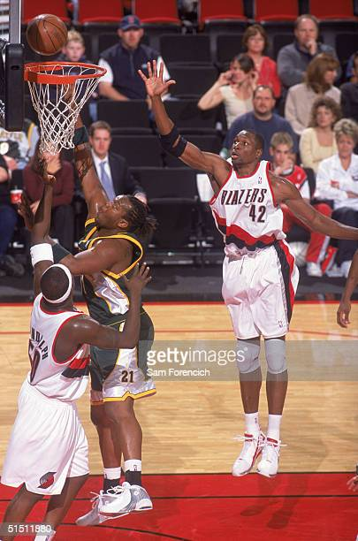 Danny Fortson of the Seattle Sonics goes to the basket against Zach Randolph and Theo Ratliff of the Portland Trail Blazers during a preseason game...