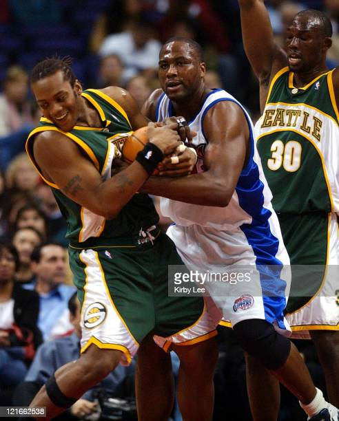 Danny Fortson of the Seattle SuperSonics and Elton Brand of the Los Angeles Clippers battle for ball as Reggie Evans of Seattle watches during the...