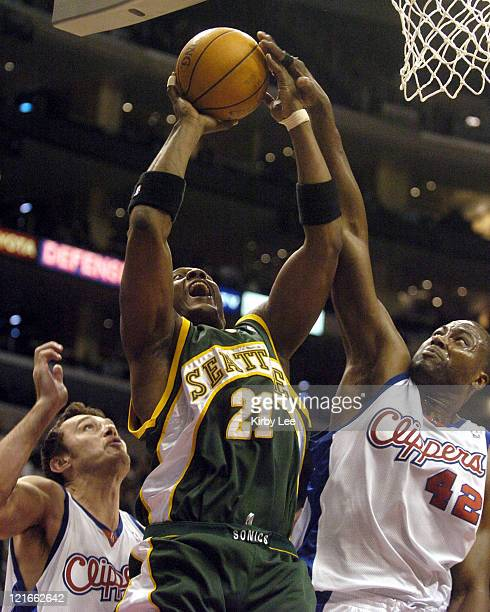 Danny Fortson of the Seattle SuperSonics is defended by Elton Brand and Zeljko Rebraca of the Los Angeles Clippers during the game between the...