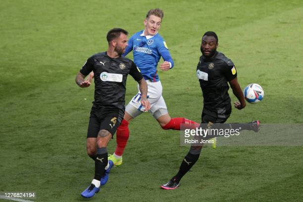 Danny Fox and Nathan Cameron of Wigan Athletic clear from Ronan Curtis of Portsmouth FC during the Sky Bet League One match between Portsmouth and...