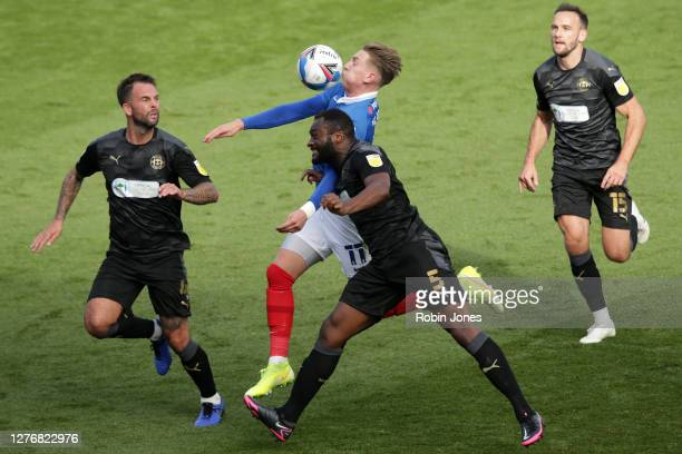 Danny Fox and Nathan Cameron of Wigan Athletic hold off Ronan Curtis of Portsmouth FC during the Sky Bet League One match between Portsmouth and...
