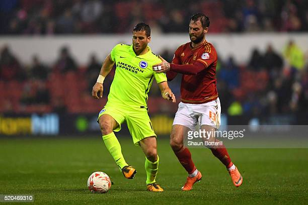 Danny Fox of Nottingham Forest makes a tackle on Tomer Hemed of Brighton and Hove Albion during the Sky bet Championship match between Nottingham...