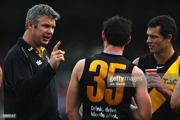 Danny Frawley coach of the Tigers speaks to Chris Newman and Andrew Kellaway during the round 18 AFL match between the Fremantle Dockers and the...