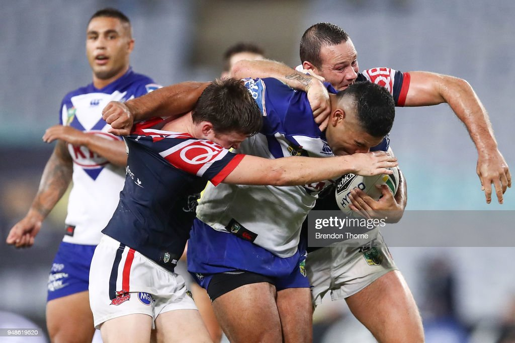 Danny Fualalo of the Bulldogs is tackled by Roosters defence during the round seven NRL match between the Canterbury Bulldogs and the Sydney Roosters at ANZ Stadium on April 19, 2018 in Sydney, Australia.