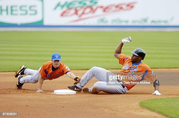 Danny Garcia is late with the tag as Cliff Floyd slides safely into second during an intrasquad game at the New York Mets' spring training camp in...