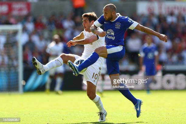 Danny Graham of Swansea City is challenged by John Heitinga of Everton during the Barclays Premier League match between Swansea City and Everton at...