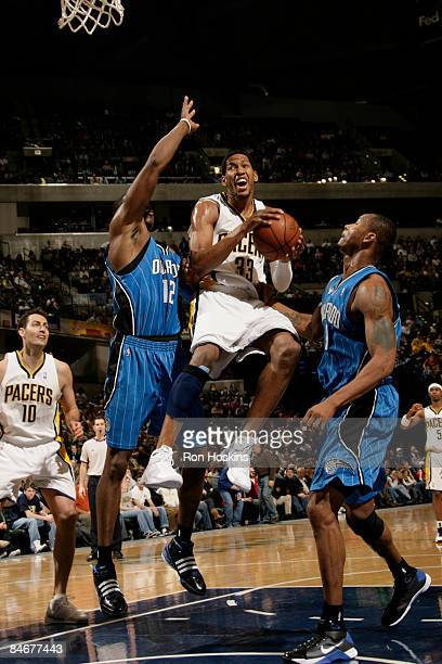 Danny Granger of the Indiana Pacers drives to the basket against Dwight Howard and Rashard Lewis of the Orlando Magic at Conseco Fieldhouse on...