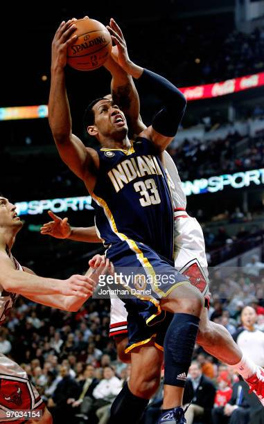 Danny Granger of the Indiana Pacers goes up for a shot between Kirk Hinrich and James Johnson of the Chicago Bulls at the United Center on February...