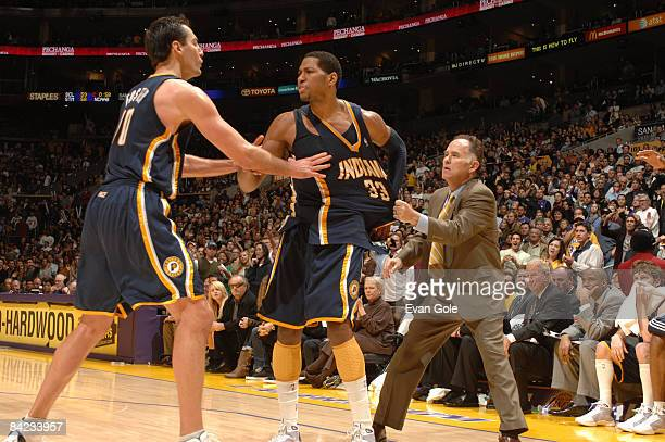 Danny Granger of the Indiana Pacers is restrained by teammate Jeff Foster and Head Coach Jim O'Brien after fouling out against the Los Angeles Lakers...