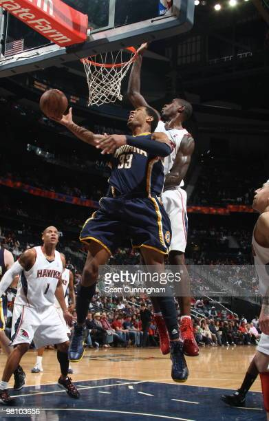 Danny Granger of the Indiana Pacers puts up a shot against Marvin Williams of the Atlanta Hawks on March 28 2010 at Philips Arena in Atlanta Georgia...