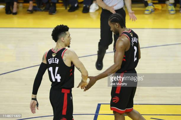 Danny Green hifives Kawhi Leonard of the Toronto Raptors during Game Three of the NBA Finals on June 5 2019 at ORACLE Arena in Oakland California...