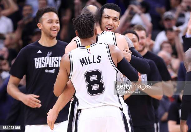 Danny Green hugs Manu Ginobili and Patty Mills of the San Antonio Spurs after an overtime win against the Houston Rockets during Game Five of the...