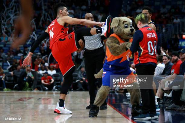 Danny Green of the Toronto Raptors kicks at Clevland Cavaliers mascot Moondog during the first half of a game against the New Orleans Pelicans at the...