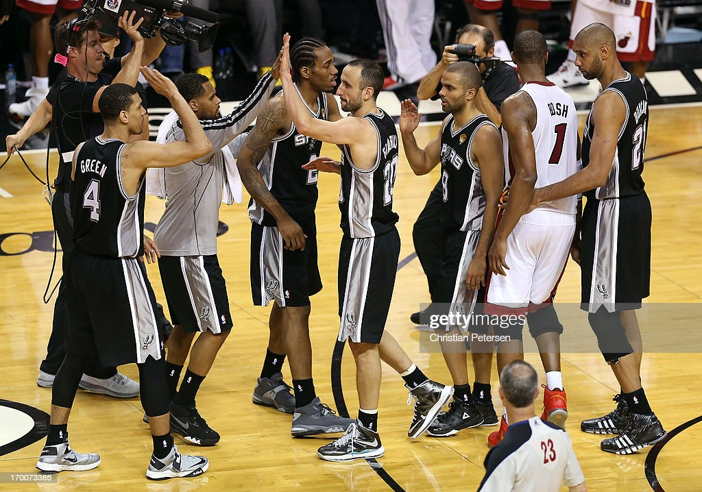 Danny Green #4, Patty Mills #8, Manu Ginobili #20, Tony Parker #9 and Tim Duncan #21 of the San Antonio Spurs celebrate after defeating Chris Bosh #1 and the rest of the Miami Heat 92-88 during Game One of the 2013 NBA Finals at AmericanAirlines Arena on June 6, 2013 in Miami, Florida.