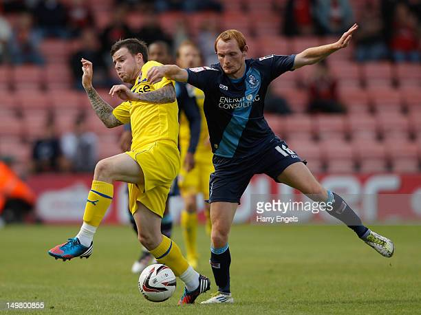 Danny Guthrie of Reading competes for the ball with Shaun MacDonald of Bournemouth during the preseason friendly match between Bournemouth and...