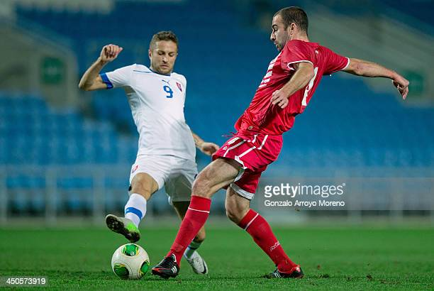 Danny Higginbotham of Gibraltar competes for the ball with Stanislav Sestak of Slovakia during the international friendly match between Gibraltar and...