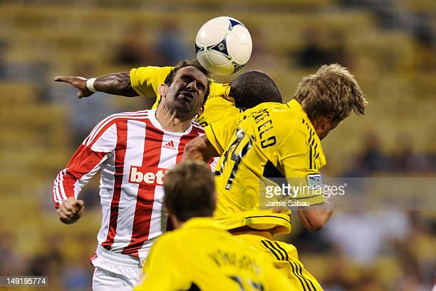 Danny Higginbotham of Stoke City FC battles for control of the ball with Aaron Schoenfeld of the Columbus Crew and Emilio Renteria of the Columbus...