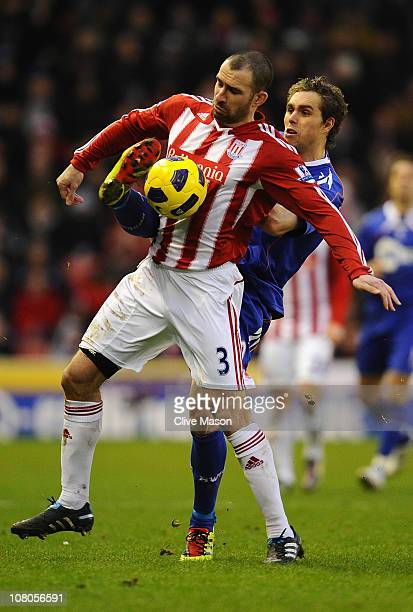 Danny Higginbotham of Stoke City is challenged by Johan Elmander of Bolton Wanderers during the Barclays Premier League match between Stoke City and...