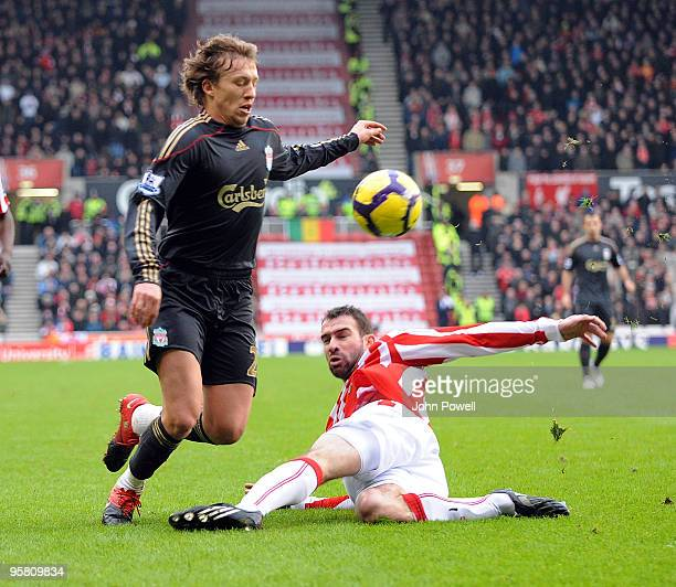 Danny Higginbotham of Stoke goes in on Lucas Levia of Liverpool during the Barclays Premier League match between Stoke City and Liverpool at...