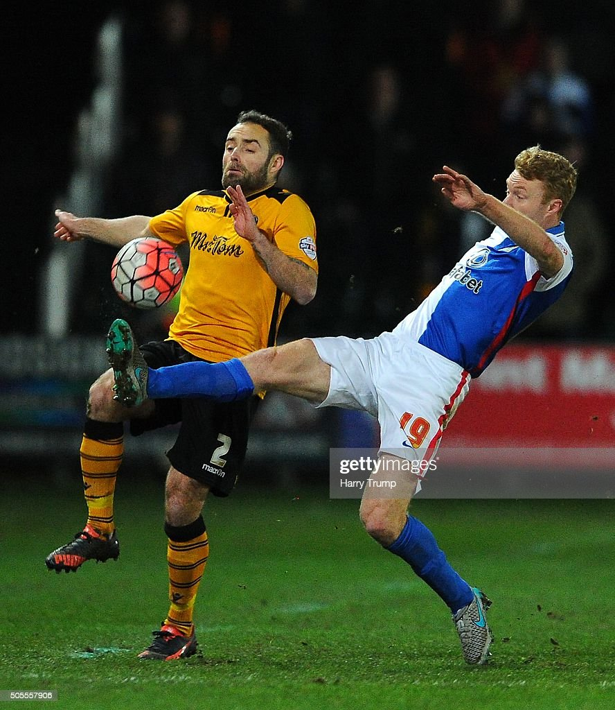 Danny Holmes of Newport County is tackled by Chris Taylor of Blackburn Rovers during the Emirates FA Cup Third Round match between Newport County and Blackburn Rovers at Rodney Parade on January 18, 2016 in Newport, Wales.