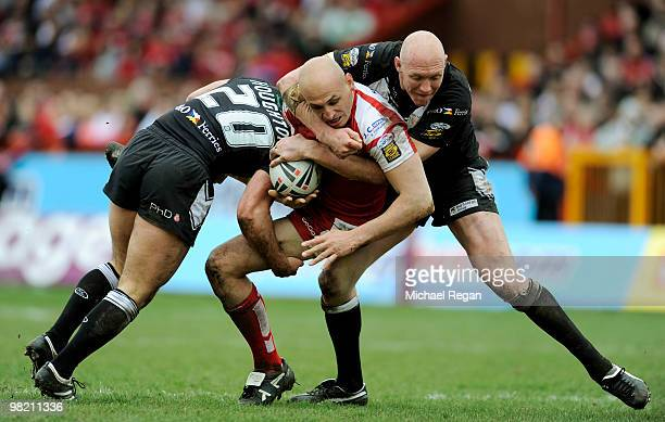 Danny Houghton and Craig Fitzgibbon of Hull FC tackle Mick Vella of Hull KR during the engage Super League match between Hull Kingston Rovers and...