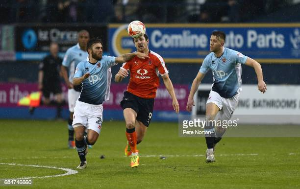 Danny Hylton of Luton Town attempts to move between Jack Payne and Will Aimson of Blackpool during the Sky Bet League Two Play off Semi Final Second...