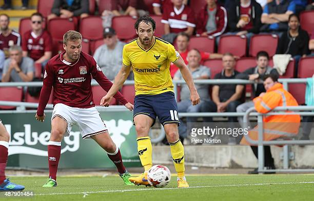 Danny Hylton of Oxford United plays the ball watchd by Joel Byrom of Northampton Town during the Sky Bet League Two match between Northampton Town...