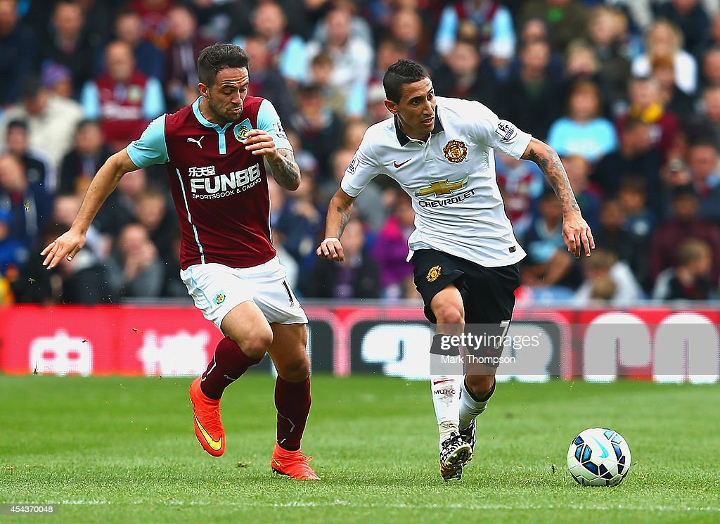 Danny Ings of Burnley and Angel di Maria of Manchester United compete for the ball during the Barclays Premier League match between Burnley and Manchester United at Turf Moor on August 30, 2014 in Burnley, England.